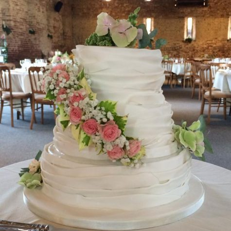 A 3 tier vintage ruffle wedding cake with fresh flowers supplied by the bride