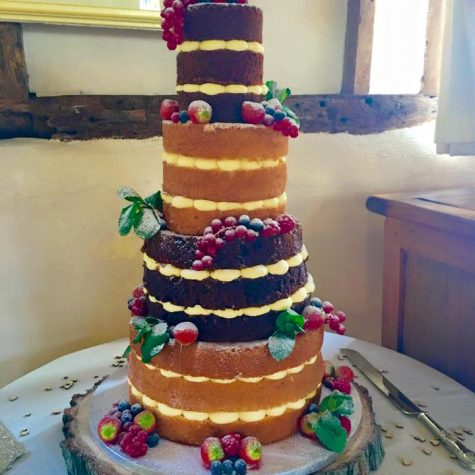 "A 4 tier, triple layer naked wedding cake, made in vanilla, carrot, lemon and chocolate sponge. Shown as a 10"", 8"", 6"" and 4"" round"