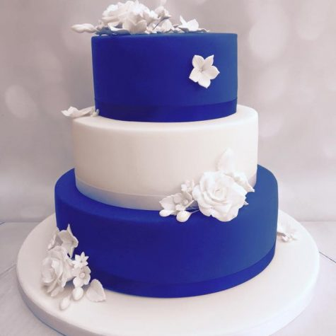 A 3 tier royal blue and white iced, sharp edged wedding cake, with handmade sugar flowers