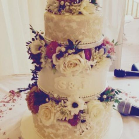 A 3 tier wedding cake encrusted with sugar lace , personalised with the bride and groom's initials