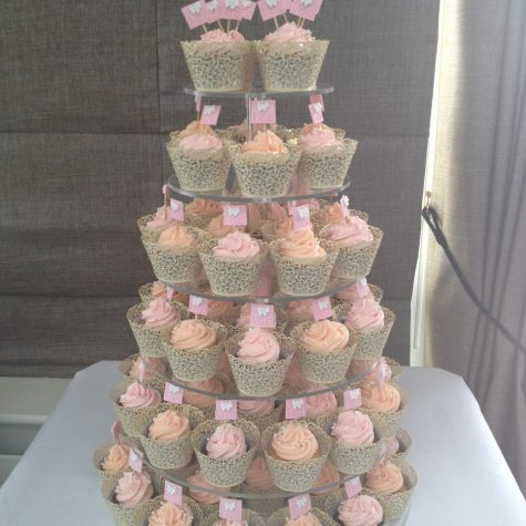 A wedding cupcake tower with cupcakes wrapped in ivory lace effect wrappers