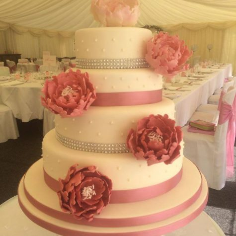 Our latest creation. A stunning 4 tier ivory iced wedding cake with 5 handmade statement sugar peonies, finished with diamanté and pink ribbon