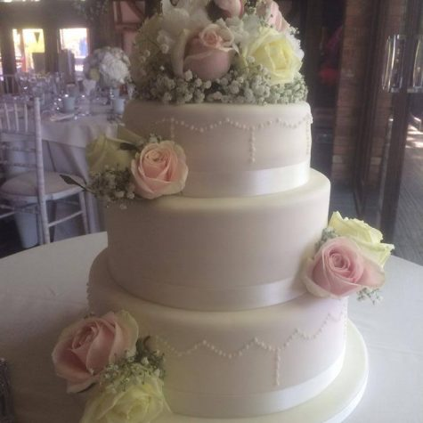 One of our latest wedding cake creations.....a three tier ivory iced cake with hand piped royal icing and fresh flowers to finish