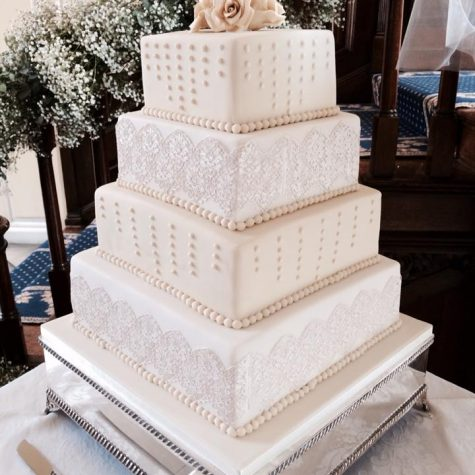 A beautiful vintage cake lace and royal iced 4 tier wedding cake, with handmade sugar roses. Made for a wedding at Gosfield Hall