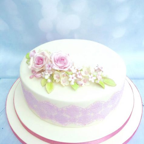 "A 12"" round single tier wedding cake, sat on double depth drum, with sugar lace and handmade sugar flower posy topper"