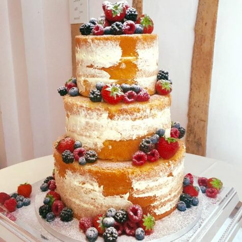 A luxury 3 tier triple layer naked wedding cake, decorated with fresh fruit