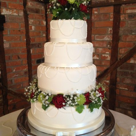 "4 tier ""pearl necklace"" wedding cake with fresh flowers. The necklaces were hand piped using royal icing"